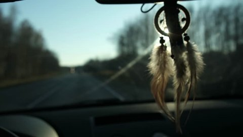 View Of Dream Catcher Hanging From Rearview Mirror Inside Car. Travel by car. View of the road and snowy mountains in the evening
