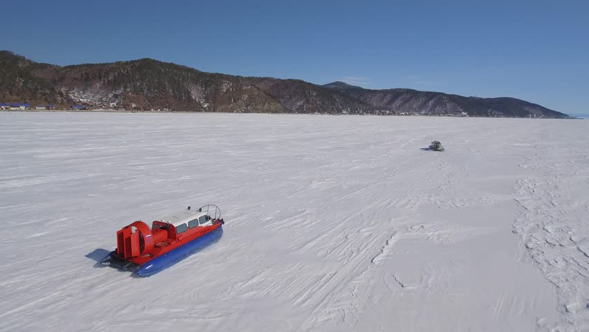 Khivus boat red transport speed hovercraft tourist attraction. Baikal lake Russia Siberia Frozen unique landscape space High rocks. Snow winter ice blue sky. Best Aerial Helicopter follow flight