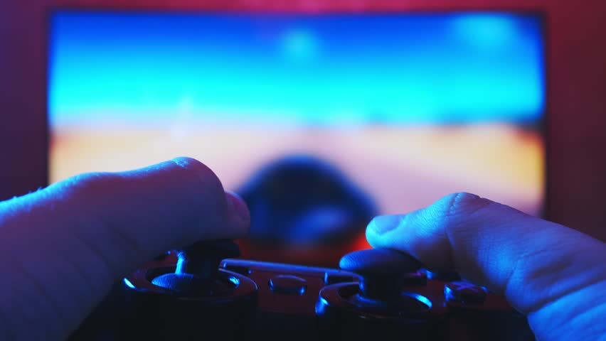Close view of a gamer's hands playing racing video game on his console using joystick