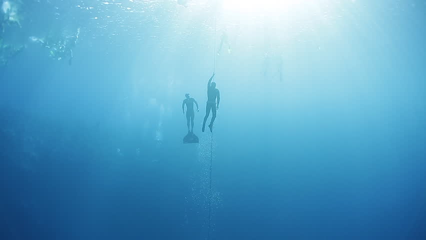 Freedivers ascend along the rope in a sea. Blue Hole, Dahab, Egypt.