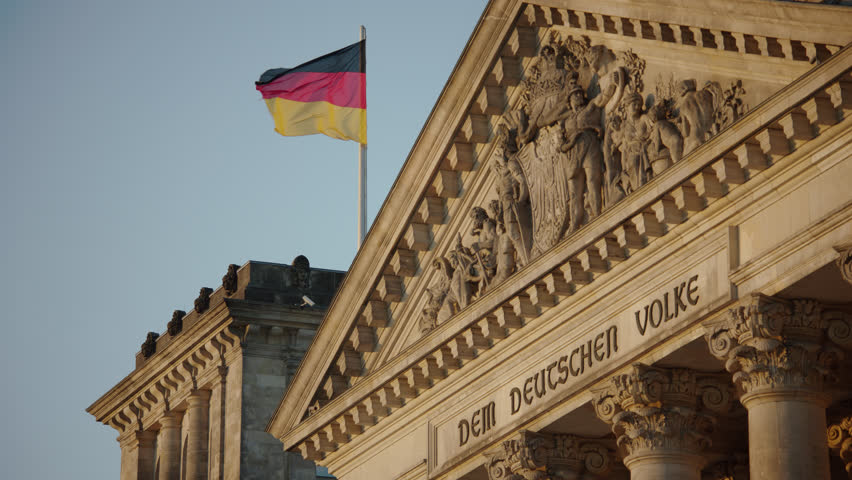 May, 2017 Berlin, Germany. Reichstag entrance inscription, sculptures, and German Flag on the front during sunset.