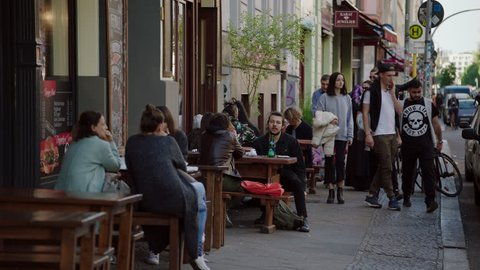 May, 2017 Berlin, Germany. People sit a restaurant as people pass by on the sidewalk in Kreuzberg in the day.