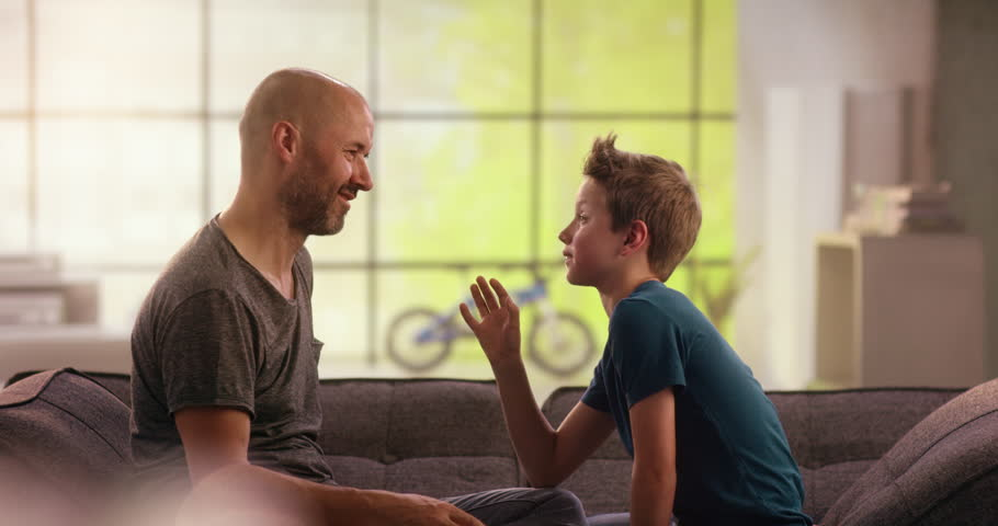 Father and son arm-wrestling on on the couch