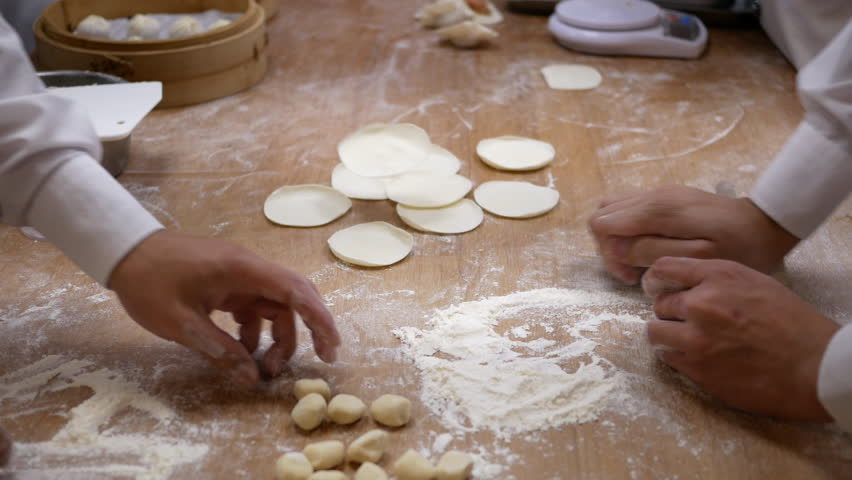 Motion of people are kneading the dough and shaping it with their hands to make dumplings in Taipei Taiwan with 4k resolution.
