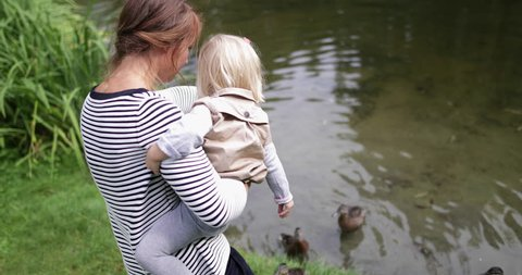 Mother and daughter feeding the ducks in park