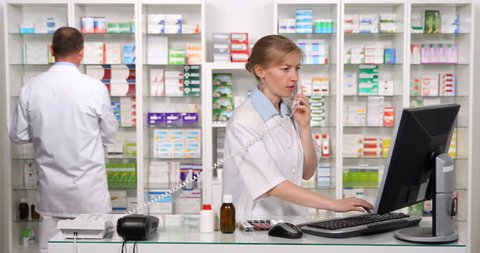 Happy Pharmacist Woman Give Positive Response Talking Landline Phone in Pharmacy