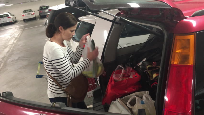 Young adult woman (age 30 -35) loading shopping grocery bags into a car in a parking lot after shopping activity in the supermarket. Consumption concept. Real people. Copy space