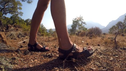 131b448a523 Legs of tourist in sandals walking on mountains trail outdoor. feet of man  going on