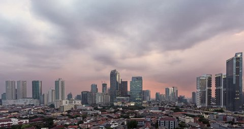 Sunset time lapse, as a day to night, with a pan to the right, over Jakarta skyline business district in Indonesia capital city. Jakarta is Indonesia capital city and the largest in Southeast Asia.