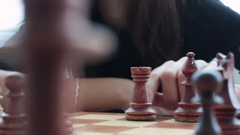 hand of a young girl makes a move with a chess piece above the chessboard in the room. Playing chess, board games.