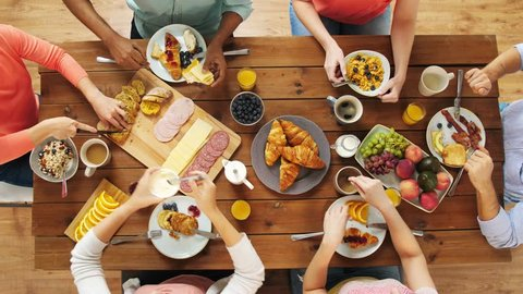 eating and leisure concept - group of people having breakfast at table with food