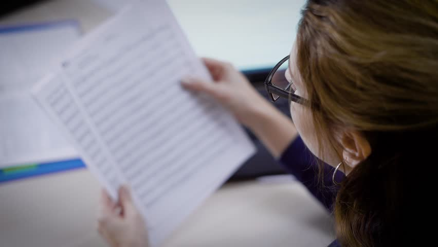 A lawyer woman is wearing glasses is reading documents in her office in daytime, jurist of a consulting company | Shutterstock HD Video #32422849