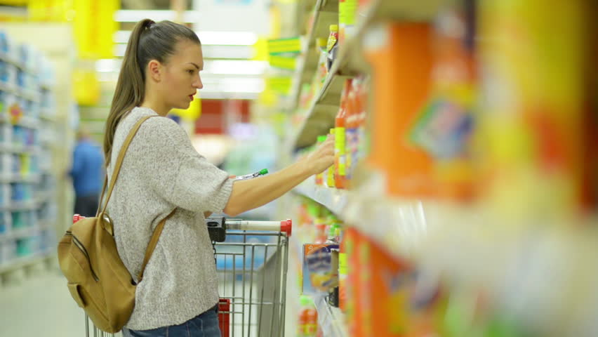 Woman with Long Dark Hair and Shopping Cart Buying Juice in the Supermarket Standing Near Shelf | Shutterstock HD Video #32432989