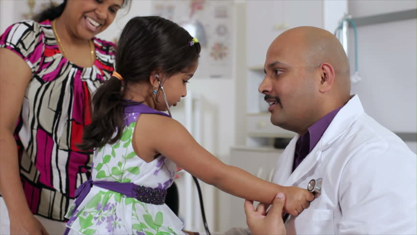 A cute little Indian girl with her mother uses a stethoscope to listen to the heart beat of her kind pediatrician.