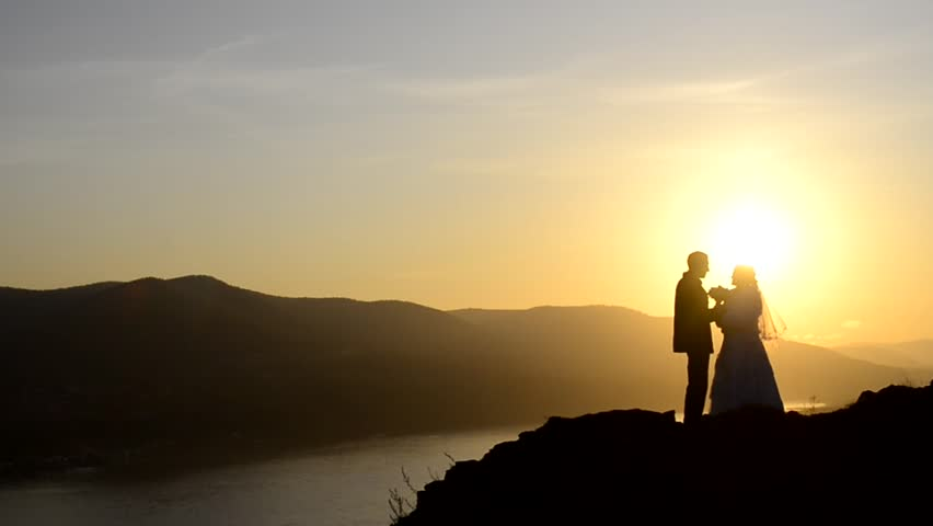 A wedding couple stands on a cliff at sunset and cuddles up to each other with love | Shutterstock HD Video #32473939
