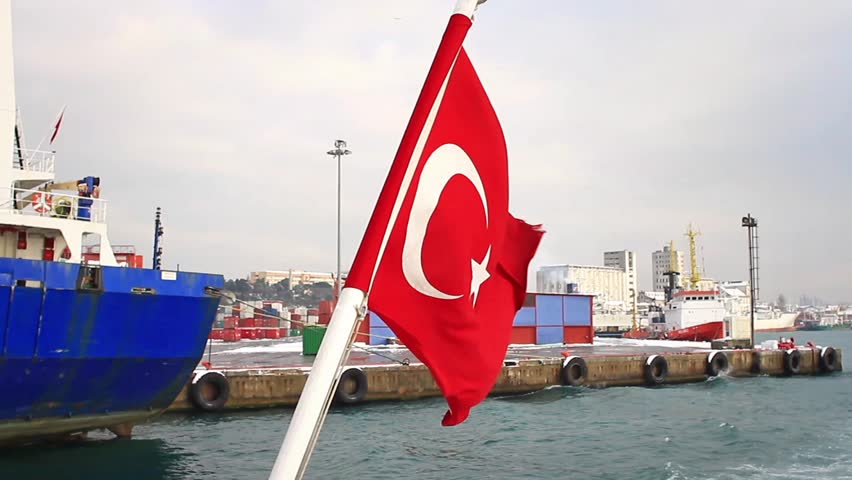 Seaport as seen from the waterside with a Turkish Flag waving. An empty container ship moored in the background. Istanbul Haydarpasa Port has a capacity of 1,200 vessels/year.