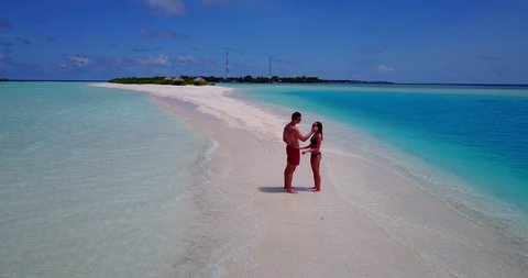 v15553 two 2 people together having fun man and woman together a romantic young couple sunbathing on a tropical island of white sand beach and blue sky and sea
