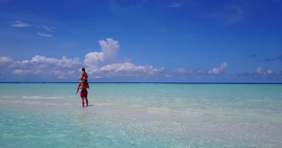 v15544 two 2 people together having fun man and woman together a romantic young couple sunbathing on a tropical island of white sand beach and blue sky and sea