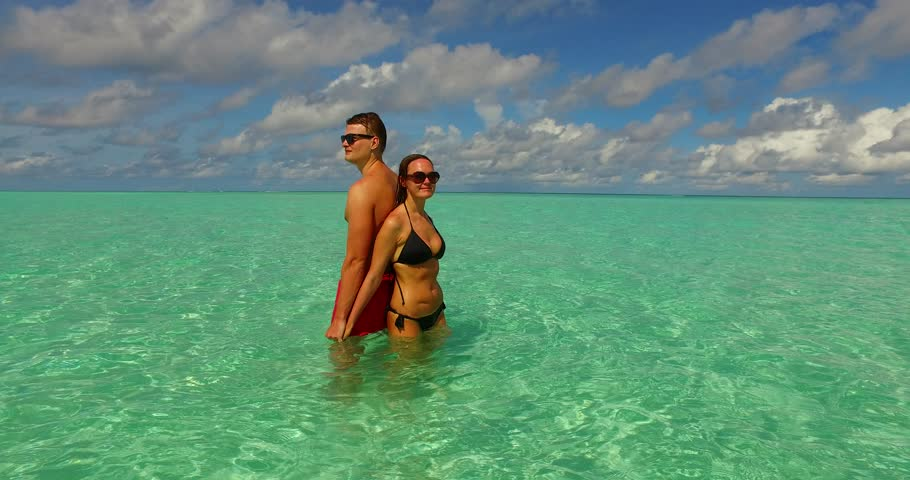 v15493 two 2 people together having fun man and woman together a romantic young couple sunbathing on a tropical island of white sand beach and blue sky and sea