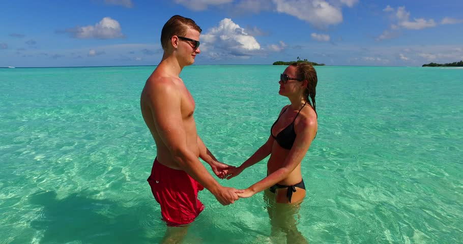 v15535 two 2 people together having fun man and woman together a romantic young couple sunbathing on a tropical island of white sand beach and blue sky and sea