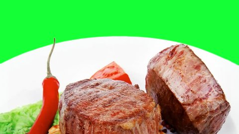 grilled beef fillet medallions with thyme and red hot chili pepper on plate over green screen slow motion hidef