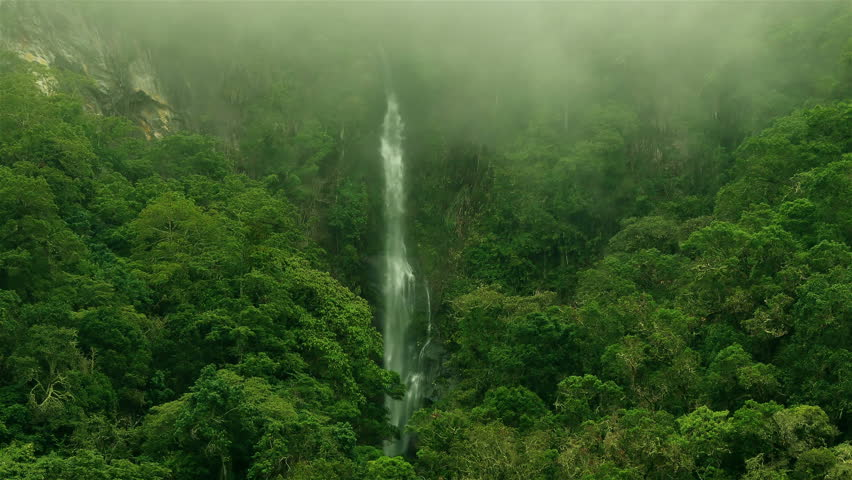 Epic waterfall Nature background full hd and 4k. High Humidity In Jungle Rainforest with a powerful waterfall. Timelapse Of Moving Clouds And Fog over a waterfall between Green mountains. Ecology.