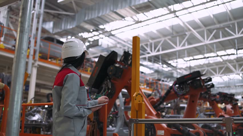 BELARUS, BORISOV - OCTOBER 19, 2017: Automobile plant, modern production of cars, robot equipment, working woman near production line, process of welding car body, October 19 in Belarus.