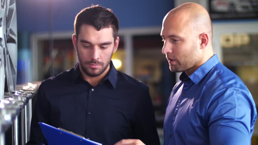 business, maintenance and people concept - male customer choosing wheel rims and talking to salesman with clipboard at car repair service or auto store