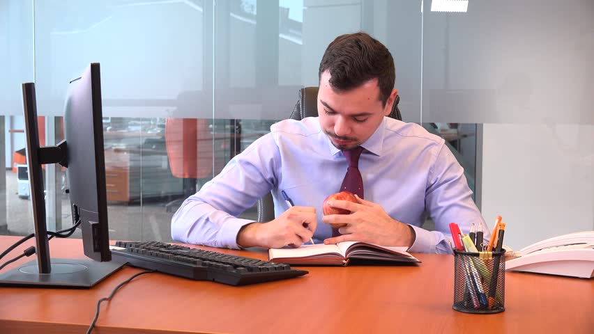 Accountant man freelancer write agenda meeting eating lunch fruit inside office | Shutterstock HD Video #32566849