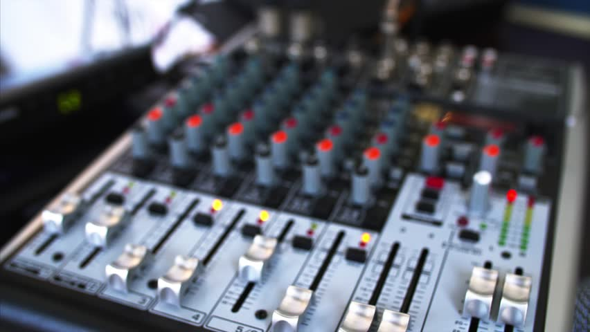 Close view of blurred sound console with many indicators, sliders, and buttos and closeup of two microphones | Shutterstock HD Video #32577859