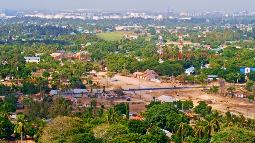 Cinematic aerial of port city Dar es Salaam downtown skyline with skyscraper buildings, lush, green vegetation, palm trees, minor vehicle traffic near Indian ocean beach, Tanzania, Africa