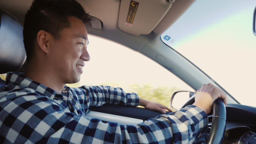 Happy Chinese man driving car, smiling