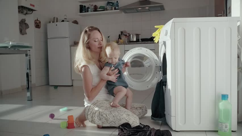 Young mother sitting on floor front washing machine and holding baby in arms. Young mother putting dirty laundry in washing machine