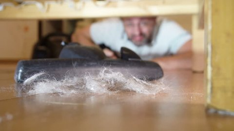 Middle-aged man cleaning a floor under a bed lying on the floor using vacuum cleaner
