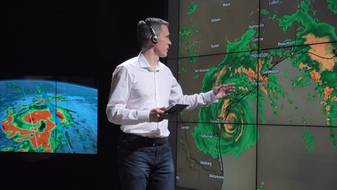A news weather reporter wearing a headset presenting a live hurricane forecast displayed on two large screens. Elements of this image furnished by NASA.
