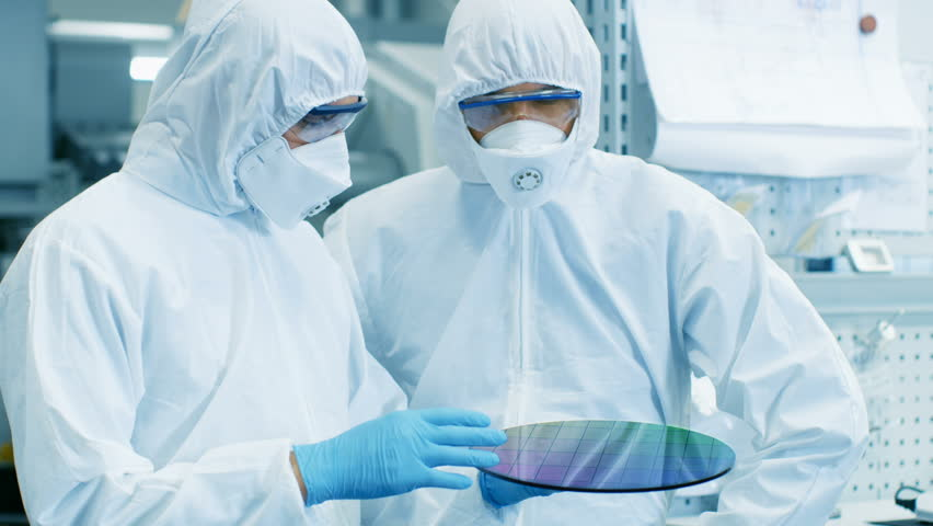 Two Scientists/ Technicians in Sterile Suits Check Semiconductor Silicon Wafer that Reflects Many Different Colors, it will be Made into Computer Chips.They Work in a Semiconductor Manufacturing Plant