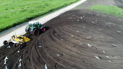 Aerial footage of tractor plowing land for initial cultivation of soil in preparation for sowing seed or planting to loosen or turn the soil stable footage also showing sea gull looking for food 4k