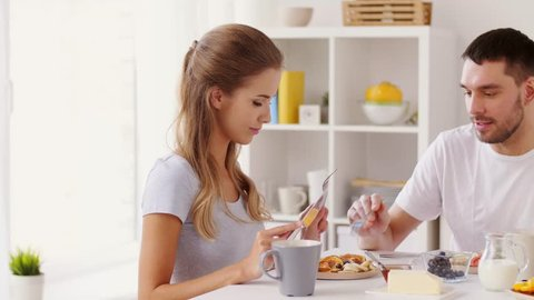 eating and people concept - happy couple having breakfast at home and sharing food
