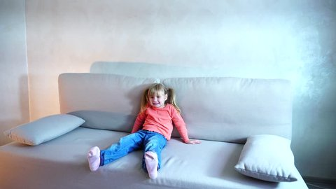 4795f54328 Smiling little blonde American girl sitting on couch in living room and  posing on camera for