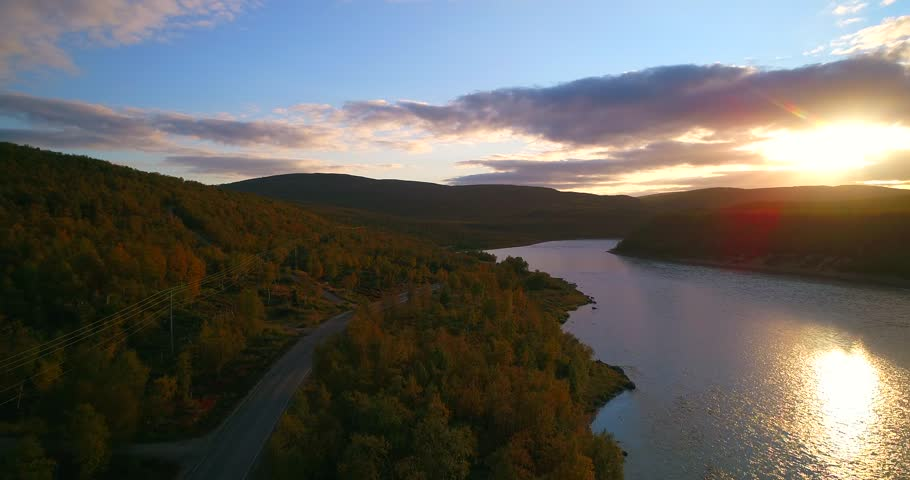 Mountain road, Cinema 4k aerial view over road 970 the tenontie, near tenojoki river, at the border of norway and utsjoki, on a sunny autumn color evening dawn, in Lapland, Lappi, Finland