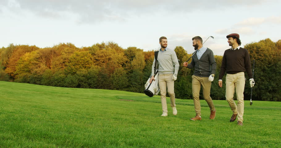 Attractive male friends walking with their clubs and bag on the golf pitch, talking and laughing.