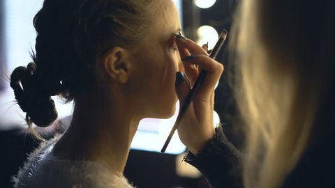 A professional make-up artist makes the girl a make-up. Dyes the eyes and lips of the model with a large brush. two blonde girls in the dressing room on the background of a mirror with lamps