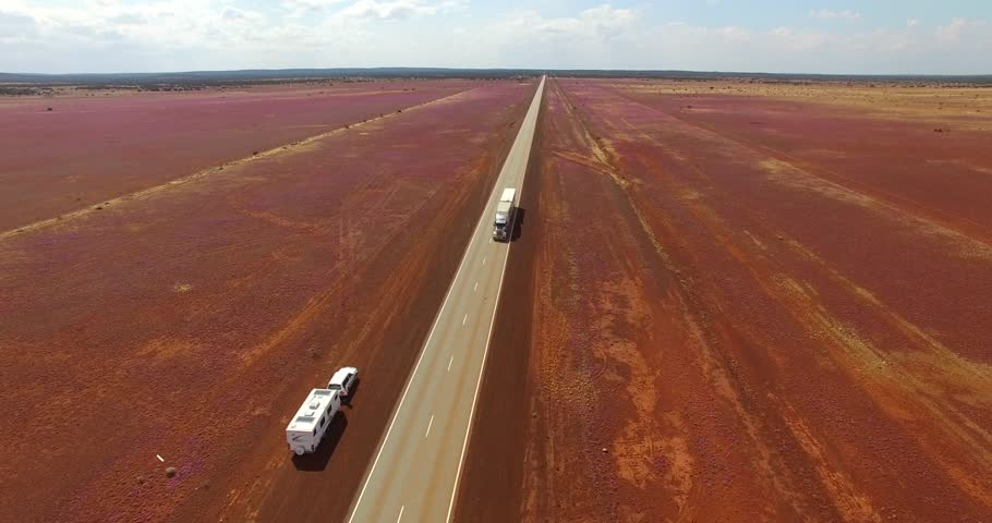 Aerial video of outback Australian highway with 4WD and caravan in the foreground and a large truck passing on an outback highway surrounded by pink wildflowers.