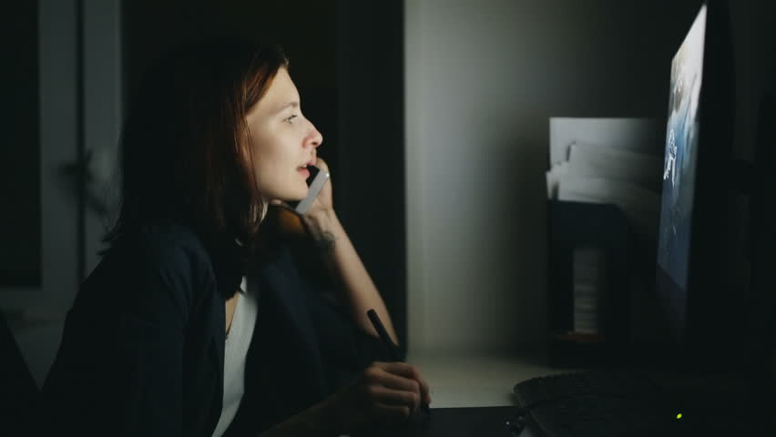 Concentrated woman designer talking phone working in office at night using computer and graphics tablet to finish job | Shutterstock HD Video #32875789
