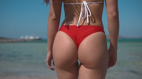 Fitness young woman buttocks walking to the sea