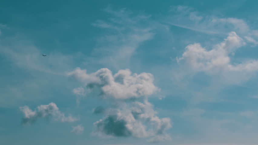 The passenger airplane is flying far in the blue sky above the clouds. Beautiful background of a flying airplane. Airplane flying deep blue sky. Commercial jet flying away far into the sky.