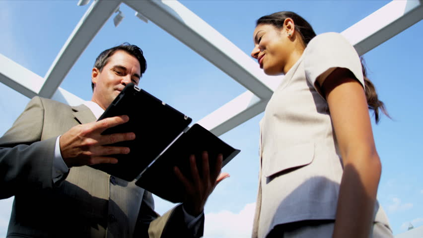 Caucasian business colleagues focusing on investment banking online tablet on rooftop office