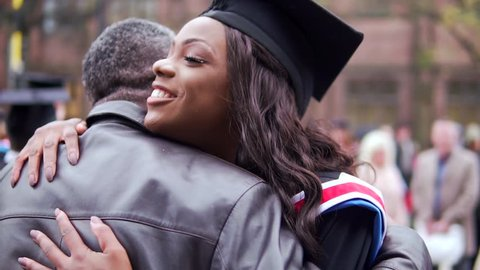 Graduation Day Celebration, With Happy Black Graduate Female Hugged By Proud Father. In Slow Motion.