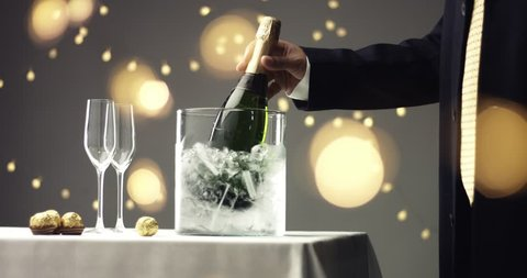 Close up video of taking a chilled bottle of sparkling wine out of a clear glass ice bucket on white, gray and golden background