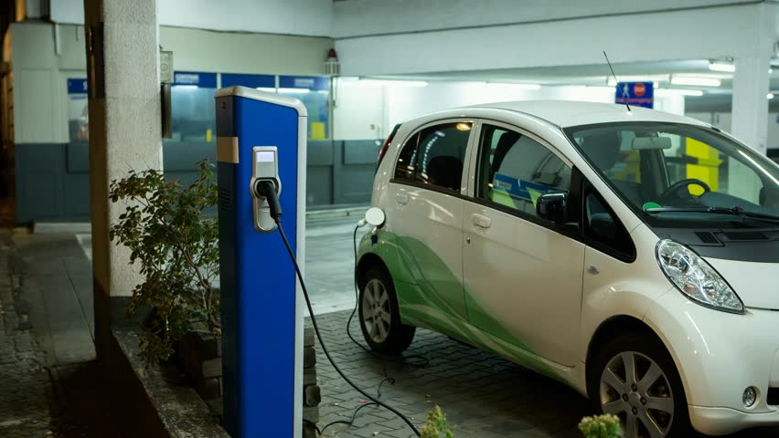 Carsharing electric car is charging in the indoor parking. The indicator on the station flashes green. Camera zoom moves on object
